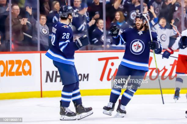 Jack Roslovic and Mathieu Perreault of the Winnipeg Jets celebrate a third period goal against the Columbus Blue Jackets at the Bell MTS Place on...