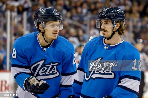 Jack Roslovic and Nic Petan of the Winnipeg Jets discuss strategy during a second period stoppage in play against the Buffalo Sabres at the Bell MTS...
