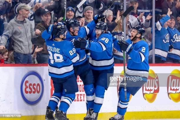 Jack Roslovic, Andrew Copp, Jansen Harkins and Anthony Bitetto of the Winnipeg Jets celebrate a third period goal against the Chicago Blackhawks at...