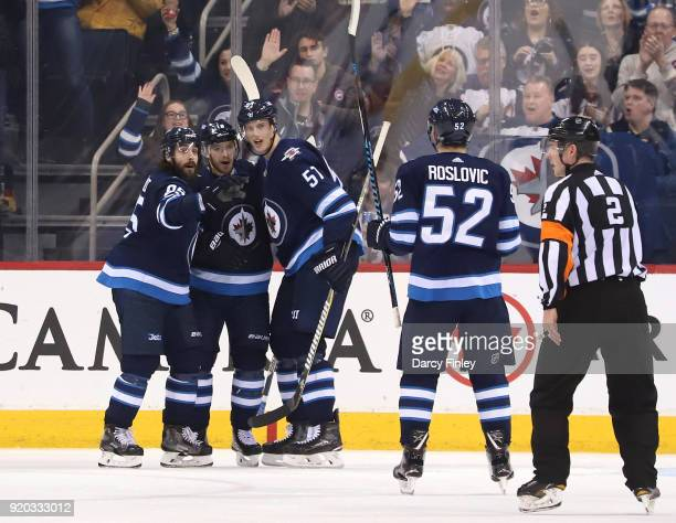 Jack Roslovic of the Winnipeg Jets joins teammates Mathieu Perreault Bryan Little and Tyler Myers as they celebrate a third period goal against the...