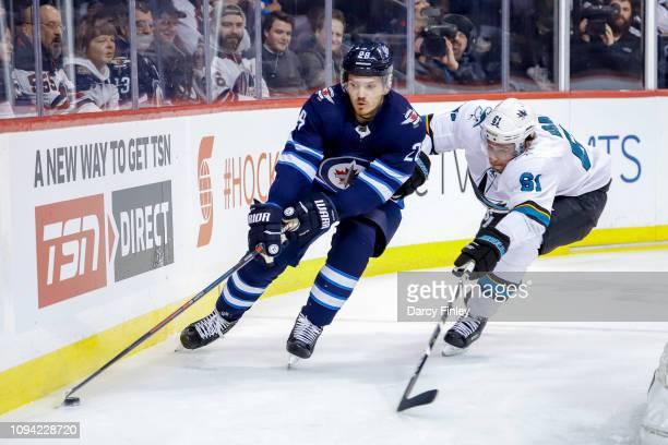 Jack Roslovic of the Winnipeg Jets plays the puck along the boards as Justin Braun of the San Jose Sharks gives chase during second period action at...