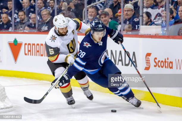 Jack Roslovic of the Winnipeg Jets plays the puck behind the net as Deryk Engelland of the Vegas Golden Knights gives chase during first period...