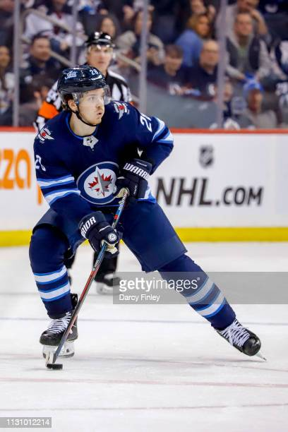 Jack Roslovic of the Winnipeg Jets plays the puck down the ice during the overtime period against the Ottawa Senators at the Bell MTS Place on...