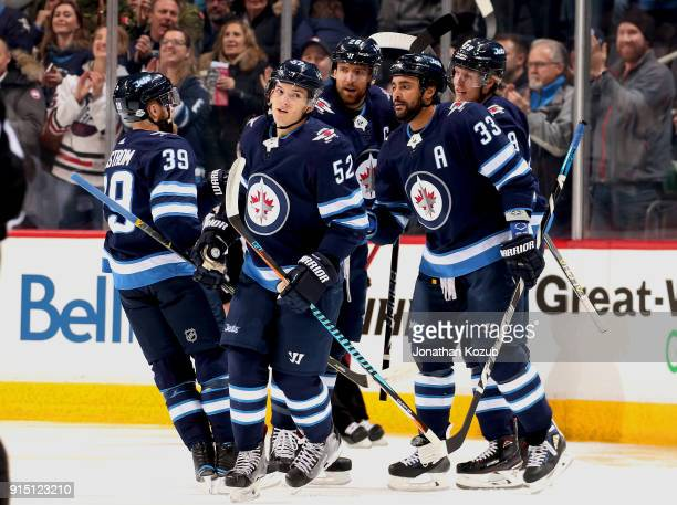 Jack Roslovic of the Winnipeg Jets skates to the bench after celebrating his first period goal against the Arizona Coyotes with teammates Toby...