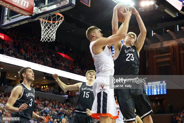 Jack Salt of the Virginia Cavaliers and Peyton Aldridge of the Davidson Wildcats fight for control of a rebound in the second half during a game at...
