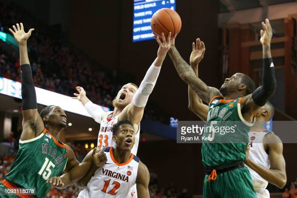 Jack Salt of the Virginia Cavaliers and Zach Johnson of the Miami Hurricanes stretch for a rebound over Ebuka Izundu of the Miami Hurricanes and...