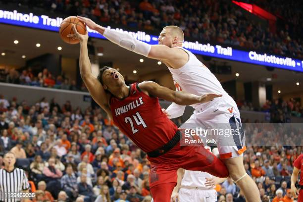 Jack Salt of the Virginia Cavaliers fouls Dwayne Sutton of the Louisville Cardinals in the first half during a game at John Paul Jones Arena on March...
