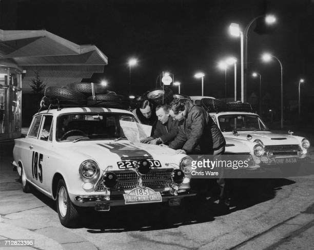 LR Jack Sears Jeff Uren and Bill Fritschey team managers for the John Willment Racing Team Ford Cortina GT prepare their route maps for the Monte...