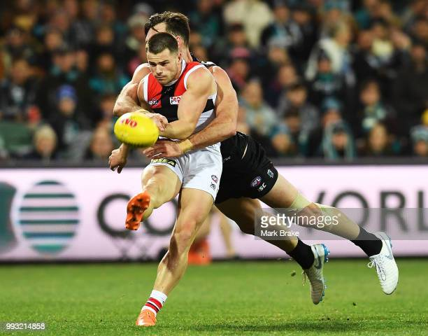 Jack Sinclair of the Saints gets the kick away under pressure from Charlie Dixon of Port Adelaide during the round 16 AFL match between the Port...