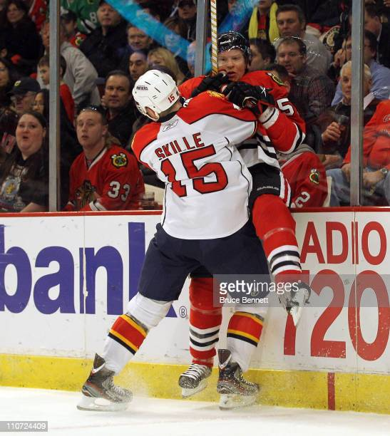 Jack Skille of the Florida Panthers boards Brian Campbell of the Chicago Blackhawks at the United Center on March 23 2011 in Chicago Illinois