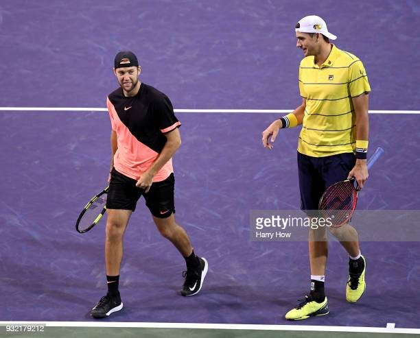 Jack Sock and John Isner of the United States laugh after winning a point in their match against Ivan Dodig of Croatia Rajeev Ram of the United...