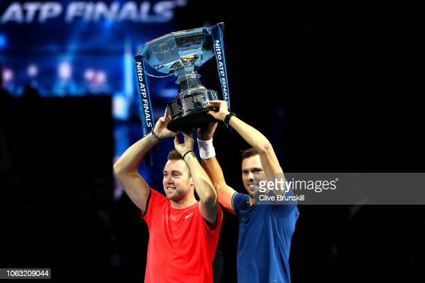 Jack Sock and Mike Bryan of The United States lift the trophy following victory following thier doubles final against PierreHugues Herbert and...