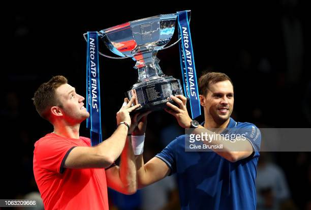 Jack Sock and Mike Bryan of The United States lift the trophy following victory following thier doubles final against Pierre-Hugues Herbert and...