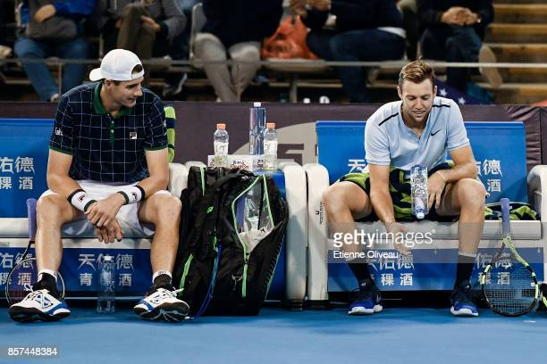 Jack Sock of the United States flips his bottle of water while his partner John Isner of the United States looks at him during their Men's double...