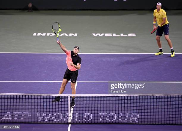 Jack Sock of the United States hits an overhead winner with John Isner of the United States in their match against Ivan Dodig of Croatia Rajeev Ram...