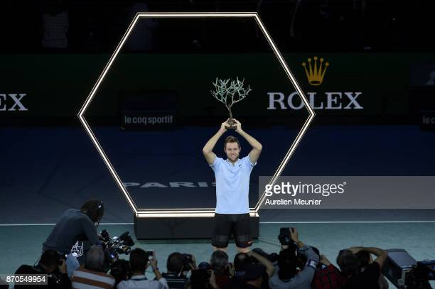 Jack Sock of the United States poses with the trophy for photographers after winning the men's singles final match against Filip Krajinovic of Serbia...