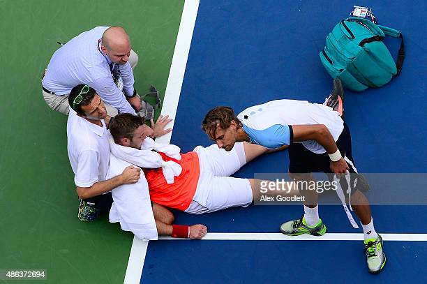 Jack Sock of the United States receives assistance from trainer Hugo Gravil for heat exhaustion as Ruben Bemelmans of Belgium talks with him during...