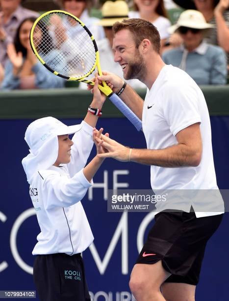 Jack Sock of the US shares a lighter moment with a ball boy during his match against Denis Shapovalov of Canada on the final day of the Kooyong...