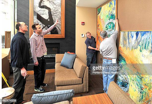 Jack Soley left gets help from Todd Dominski as they hang art pieces by Alison Haldreth of Portland with the help of Tim Grobbin and Andrew Roberts...