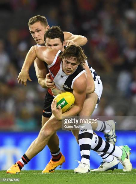 Jack Steven of the Saints handballs whilst being tackled by Patrick Dangerfield and Joel Selwood of the Cats during the round five AFL match between...