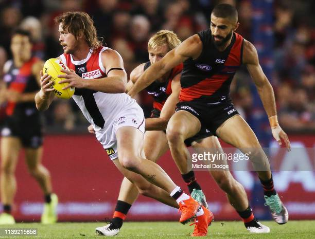 Jack Steven of the Saints runs with the ball from Adam Saad of the Bombers during the round two AFL match between the Essendon Bombers and the St...