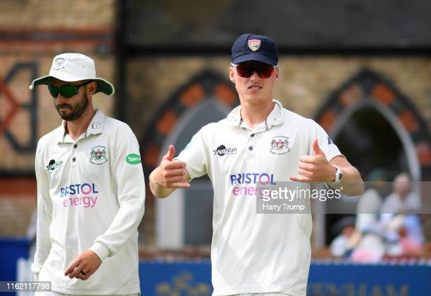 Jack Taylor and Miles Hammond of Gloucestershire make their way out to field during Day One of the Specsavers County Championship Division Two match...