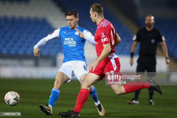Jack Taylor of Peterborough United is challenged by Connor Hall of Chorley FC during the FA Cup Second Round match between Peterborough United and...