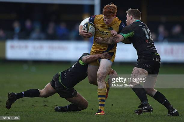 Jack Tovey of Bristol is tackled by Jonathan Spratt and Joe Thomas of Ospreys during the Anglo Welsh Cup match between Ospreys and Bristol Rugby at...