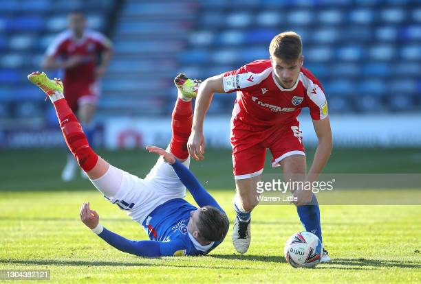 Jack Tucker of Gillingham FC evades a tackle by Ronan Curtis of Portsmouth FC during the Sky Bet League One match between Portsmouth and Gillingham...