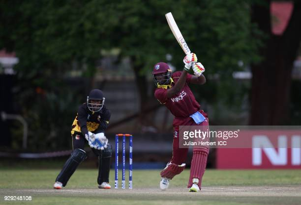 Jack Vare Kevere looks on as Jason Holder of The West Indies hits out during The Cricket World Cup Qualifier between The West Indies and Papua New...