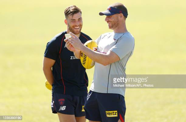 Jack Viney of the Demons and Simon Goodwin, Senior Coach of the Demons look at a mobile phone during the Melbourne Demons training session at HBF...