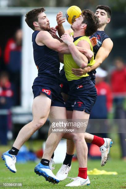 Jack Viney of the Demons back in full training for the first time since injury collides with Angus Brayshaw and Christian Petracca during a Melbourne...