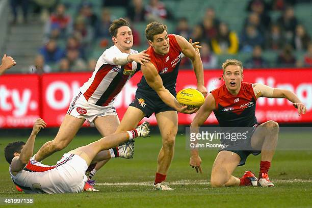 Jack Viney of the Demons handballs whilst being tackled by Jack Steven of the Saints during the round 17 AFL match between the Melbourne Demons and...