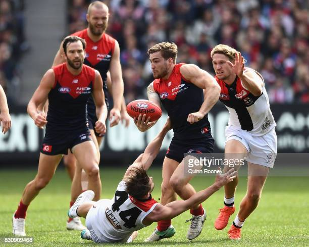 Jack Viney of the Demons handballs whilst being tackled by Maverick Weller of the Saints during the round 21 AFL match between the Melbourne Demons...