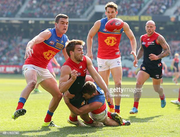 Jack Viney of the Demons handballs whilst being tackled by Pearce Hanley of the Lions during the round 16 AFL match between the Melbourne Demons and...