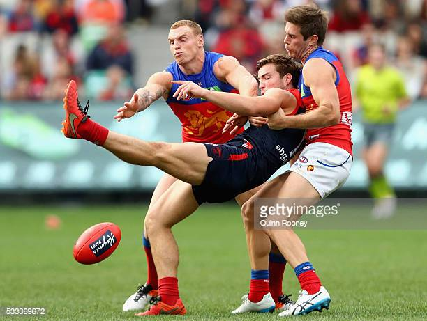 Jack Viney of the Demons kicks whilst being tackled by Mitch Robinson and Ryan Bastinac of the Lions during the round nine AFL match between the...