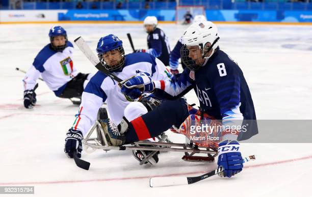 Jack Wallace of United States battles for the puck with Gianluigi Rosa of Italy in the Ice Hockey semi final game between United States and Italy...