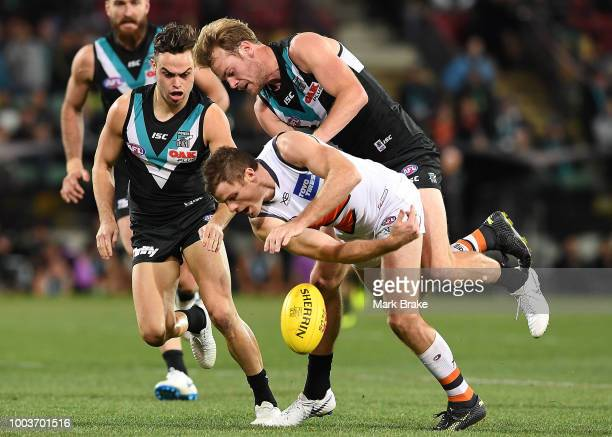 Jack Watts of Port Adelaide tackles Jacob Hopper of the Giants during the round 18 AFL match between the Port Adelaide Power and the Greater Western...