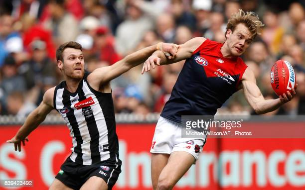 Jack Watts of the Demons and Matthew Scharenberg of the Magpies compete for the ball during the 2017 AFL round 23 match between the Collingwood...