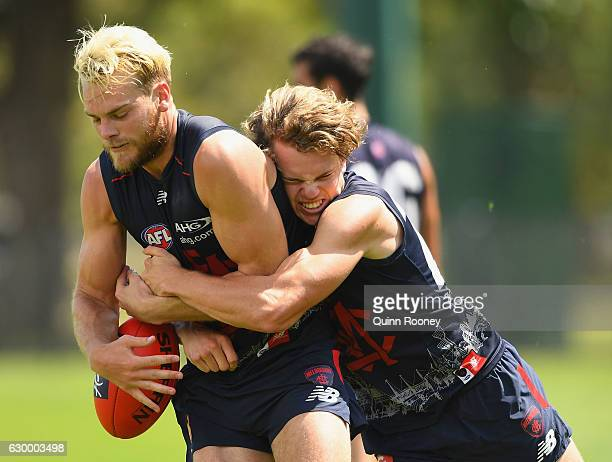 Jack Watts of the Demons is tackled by Jayden Hunt during a Melbourne Demons AFL training session at Gosch's Paddock on December 16 2016 in Melbourne...