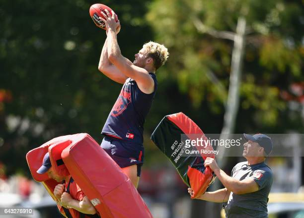 Jack Watts of the Demons marks as head coach Simon Goodwin hits him with a padded bag during a Melbourne Demons AFL training session at Gosch's...