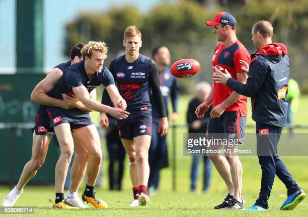 Jack Watts of the Demons passes the ball to Simon Goodwin coach of the Demons during a Melbourne Demons AFL training session at Gosch's Paddock on...