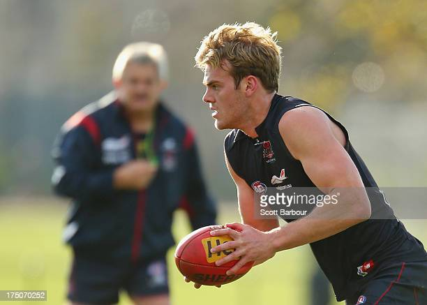 Jack Watts of the Demons runs with the ball as Neil Craig coach of the Demons looks on during a Melbourne Demons AFL training session at Gosch's...