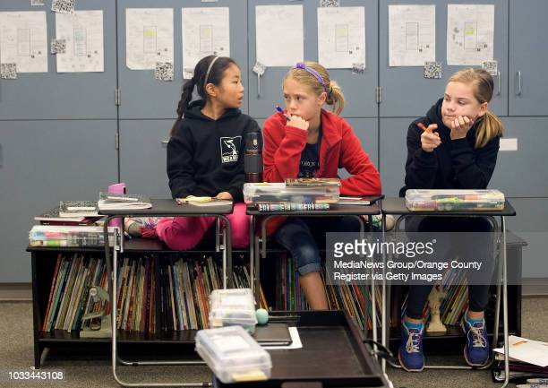 Jack Weaver fifth graders Serina Yamauchi from left Zoee Smith and Jordan Dudderar all 10 sit on a bookshelf bench and use TV trays as desks The...