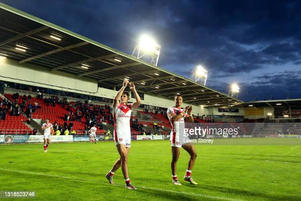 Jack Welsby and Regan Grace of St Helens applaud the fans after the Betfred Super League match between St Helens and Salford Red Devils at Totally...