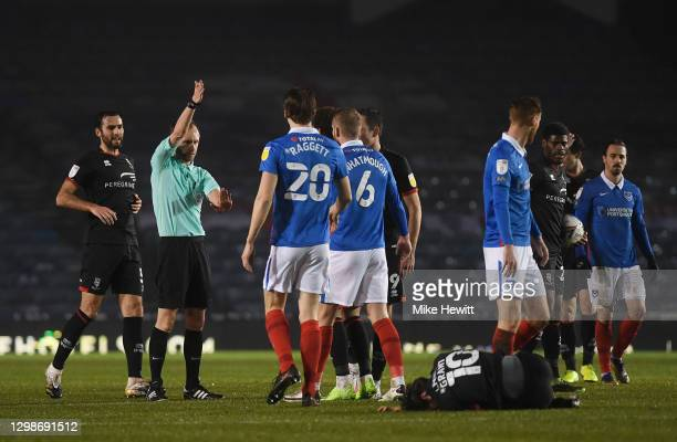 Jack Whatmough of Portsmouth FC is shown a red card by referee Sam Purkiss for a foul on Jorge Grant of Lincoln City who reacts while on the ground...