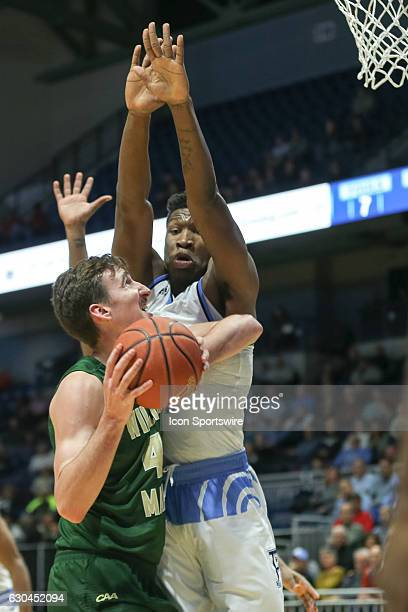 Jack Whitman forward for William Mary tries to shoot despite some solid defense during the game between the University of Rhode Island Rams and the...