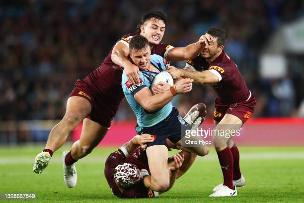 Jack Wighton of the Blues is tackled by TinoFa'asuamaleaui and Ben Hunt of the Maroons during game three of the 2021 State of Origin Series between...
