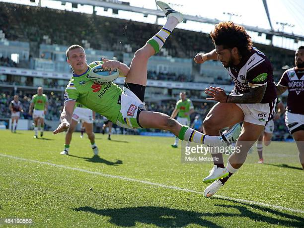 Jack Wighton of the Raiders and Jorge Taufua of the Sea Eagles collide in mid air during the round 23 NRL match between the Canberra Raiders and the...