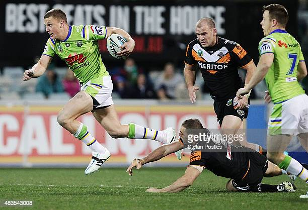 Jack Wighton of the Raiders gets past Robbie Farah of the Tigers during the round 22 NRL match between the Canberra Raiders and the Wests Tigers at...